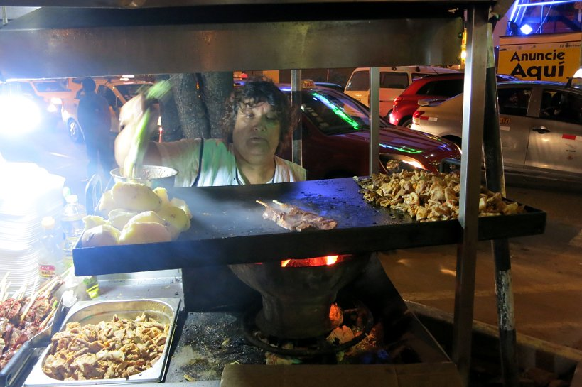 Lady selling peruvian street food in Lima by Authentic Food Quest