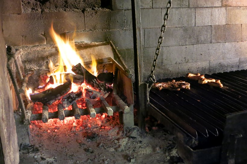 Argentinian grilling with wood fire burning separately from the meat