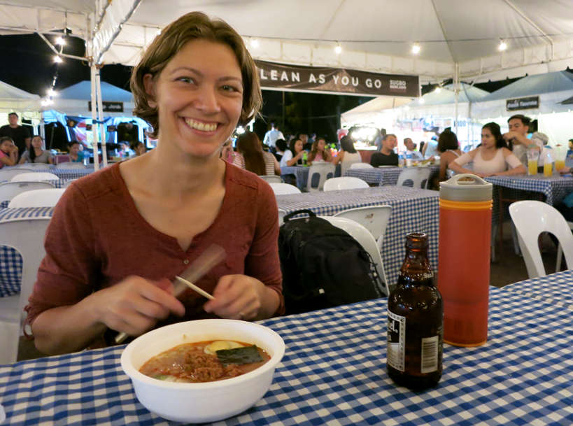 Claire at a street fair in the Philippines drinking water from a Grayl bottle in Southeast Asia Authentic Food Quest