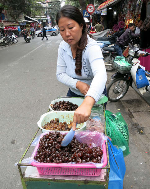 Lady selling O Mai dry fruits Vietnamese Desserts in Hanoi by AuthenticFoodQuest