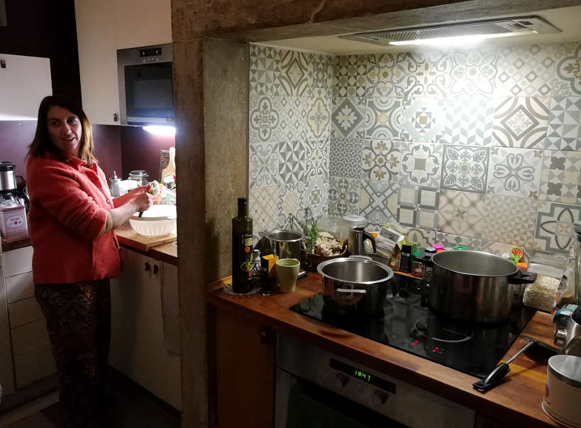 Cristina in her kitchen for Portuguese food and Portuguese Dinner while Eating with Portuguese family by Authentic Food Quest. Making traditional Portuguese food. Setting for a delightful Portuguese dinner.