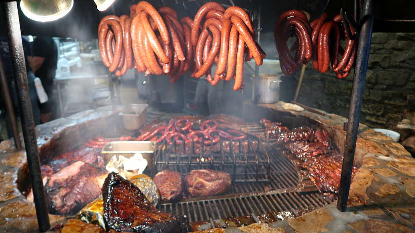 Meat cooking on the Pit at Salt Lick for Best BBQ in Lockhart for Authentic Food Quest. Rated top bbq in Lockhart BBQ reviews, Salt Lick is worth the drive from Austin for the best barbecue in Texas.
