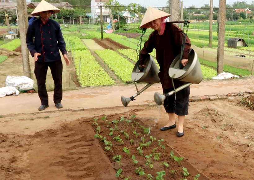 Claire Watering The plot in Tra Que Village by Authentic Food Quest