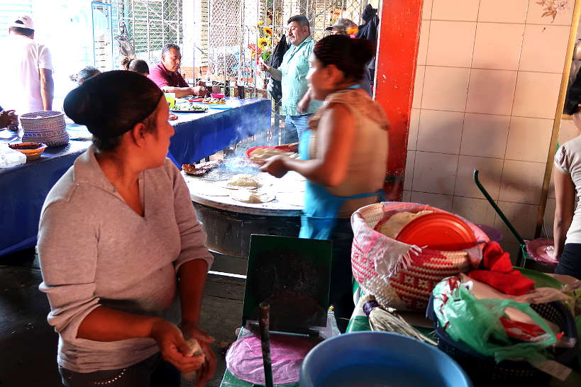 Oaxacan ladies cooking tortillas at Mercado de Abastos for cooking class in Oaxaca by Authentic Food Quest