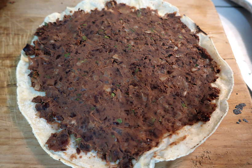 Refried beans on tortilla for tlayuda recipe by Authentic Food Quest