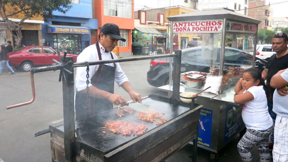 dona pochita street cart Grilling Anticuchos a popular peru street food in Lima by Authentic Food Quest