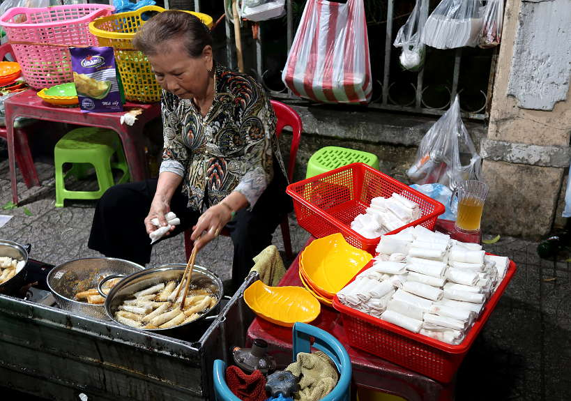 Vietnamese street food vendor making fried spring rolls by Authentic Food Quest