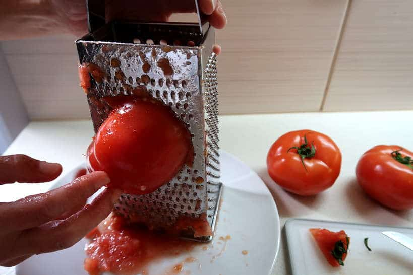 Grating tomatoes for dakos salad by Authentic Food Quest